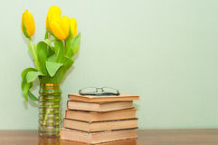 Old books with a bouquet of tulips on a wooden table Stock Images