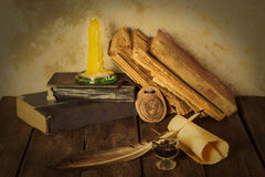 Old books, candle and feather amulet with ink Royalty Free Stock Image