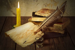 Old books, candle and feather with inks Stock Photography