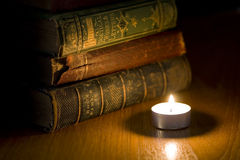 Old books by candle light. A pile of old books next to a small candle Royalty Free Stock Photography