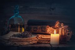 Old books and candle, tincture or potion bottle, glass of beverage and bunch of dry healthy herbs. Old books and candle, tincture or potion bottle, glass of royalty free stock photos