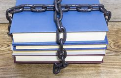 Old books with chain and padlock on wooden table. royalty free stock photos