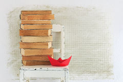Old books, chair and red paper boat Stock Photo
