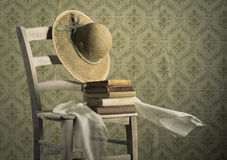 Old books on a chair with straw hat Royalty Free Stock Image
