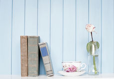 Old books, china cup and rose in the bottle on bookshelf Royalty Free Stock Image