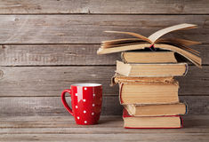 Old books and coffee cup. In front of wooden wall. With copy space Stock Image