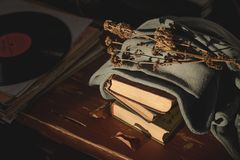 Old books covered with a cloth with a dry flower on top lie on the table and an old vinyl record stock photography