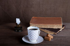 Old books, cup of coffee, candy and ancient candle on the table. Stock Photography