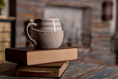 Old books and cup of coffee on wooden grunge table over fireplace background.Composition with stack of books and cup of stock photos