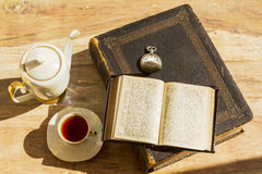 Old books and a cup of tea. A combination of antiques. old books, watch and a teapot along with a cup of tea royalty free stock photo