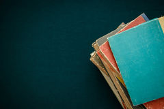 Old books on dark green background. A stack of old worn books on a dark green background with copy space Stock Image
