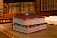Old books on a desk. Old hardback books on a wooden desk in a quiet library Stock Image