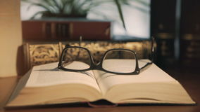 Old books on desktop with modern glasses stock video
