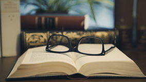 Old books on desktop with modern glasses stock footage