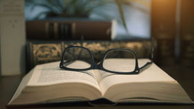 Old books on desktop with modern glasses stock video footage