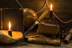 Old books and documents, a burning candle, globe and dirk stand on a wooden surface. Items on the marine theme, books and burning candles, old documents and a stock photo