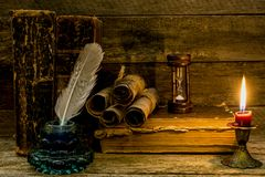Old books and documents, a burning candle, hourglass and inkwell stand on a wooden surface stock photography