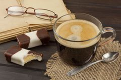 Old books, eyewear and cup of coffee on a dark wooden table. Reading vintage old book and coffee. Royalty Free Stock Images