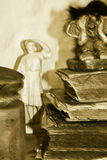 Old books and female sculpture. A troll is sitting on very old books next to female sculpture Royalty Free Stock Images