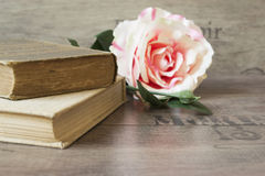 Old books and flower rose on a wooden background. Romantic floral frame background. Picture of a flowers lying on an antique book Stock Photo
