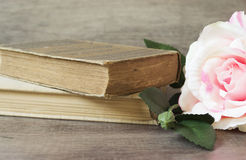 Old books and flower rose on a wooden background. Romantic floral frame background. Picture of a flowers lying on an antique book. Flowers on vintage wood Royalty Free Stock Photos