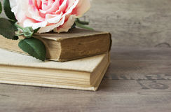 Old books and flower rose on a wooden background. Romantic floral frame background. Picture of a flowers lying on an antique book Royalty Free Stock Photos