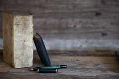 Old Books and Fountain Pen with Wooden Background. Old Books and Fountain Pen on Weathered Wooden Surface with Wooden Background and Copy Space Stock Image