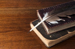 Old books and a fountain pen. On wooden table background royalty free stock photo