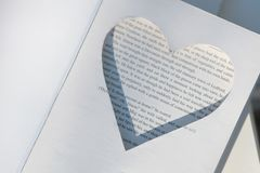 On old books, a frame in the shape of a heart is cut out. Place for rings. Wedding concepts stock photos
