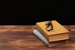 Old books and glasses on wooden background stock photo