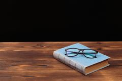 Old books and glasses on wooden background. Image stock image