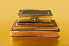 Old books on golden surface. Some old books in horizontal position on a golden reflective surface Royalty Free Stock Photo
