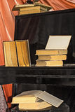 Old books lay on the piano Royalty Free Stock Photos