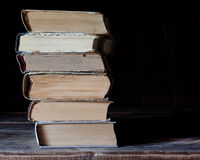 Old books lie on top of each other. Dark background Royalty Free Stock Photos