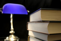 Old books with light. Books piled up for some great reading, with a lamp Royalty Free Stock Images