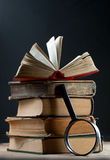 Old books with magnifying glass Royalty Free Stock Photo