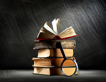 Old books with magnifying glass Royalty Free Stock Photos
