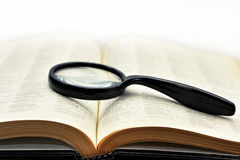 Old books with magnifying glass. Stock Image
