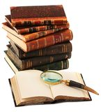 Old books with magnifying glass. Some old books with opened book and magnifying glass in the front  on white background Royalty Free Stock Photo