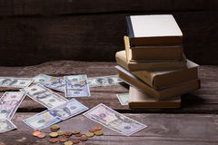 Old books and money on a vintage wooden background. Royalty Free Stock Photography
