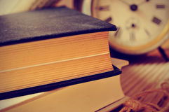 Old books and an old alarm clock, with a retro effect Royalty Free Stock Photos