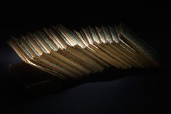 Old books, papers, ink pen and inkpot on black. Background royalty free stock image