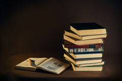 Old books and Pen. Pile of old books and pen on a dark background Royalty Free Stock Images