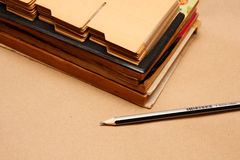 Old books and pencil. The old books and pencil on brown paper Royalty Free Stock Photos