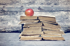 Old books. Pile of old books and one red apple Stock Images