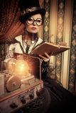Old books. Portrait of a beautiful steampunk woman over vintage background Royalty Free Stock Images