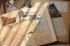 Old books, postcards and letters. Correspondence, postcards and photos over hundred years old on on beige book and atlas background Stock Image