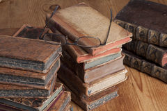 Old books and reading glasses. Vintage books are stacked on a wooden table with a pair of reading glasses on top Royalty Free Stock Photo