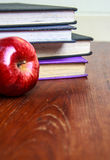 Old books and red apple  on wooden table Stock Photos