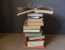 Books on a pile with glasses on top. Old books red orange white on a pile with glasses on the top background grey isolated Stock Images